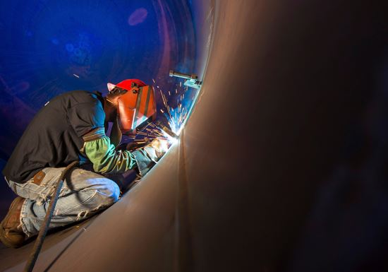 Employee welding inside of large pressure vessel tank